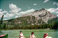 A man photographs two women in a canoe on the Bow River