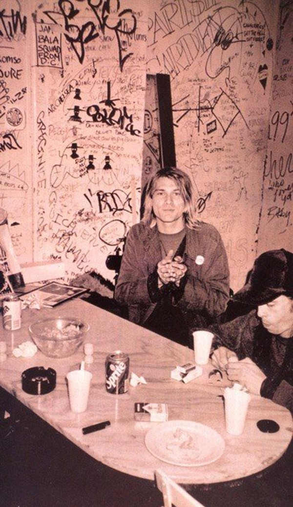 Kurt Cobain surrounded by graffiti and Dave Grohl