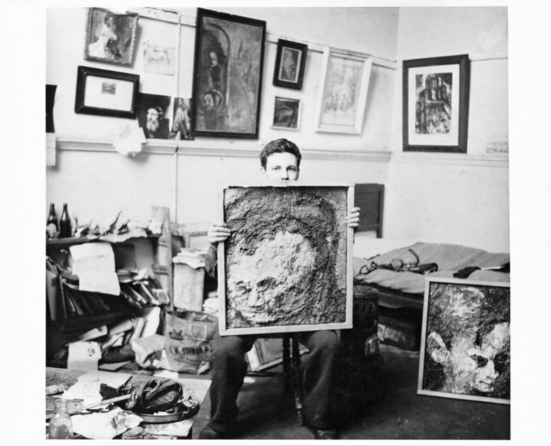 Frank in the studio with portraits of Leon Kossoff