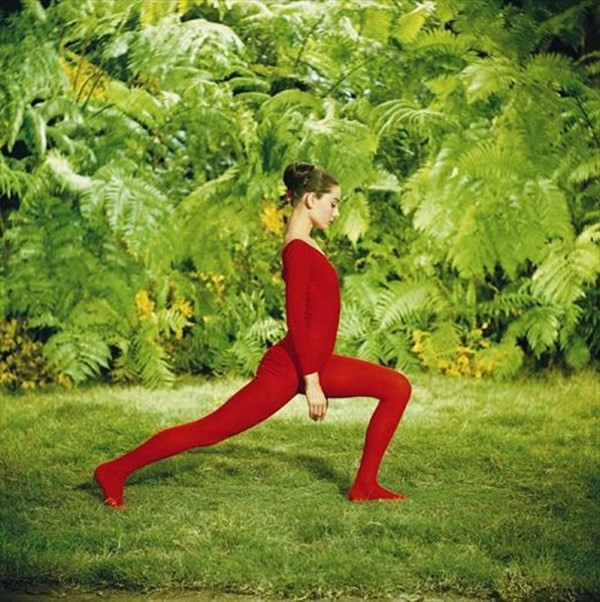 Dressed in a striking red leotard, Audrey exercises in the g
